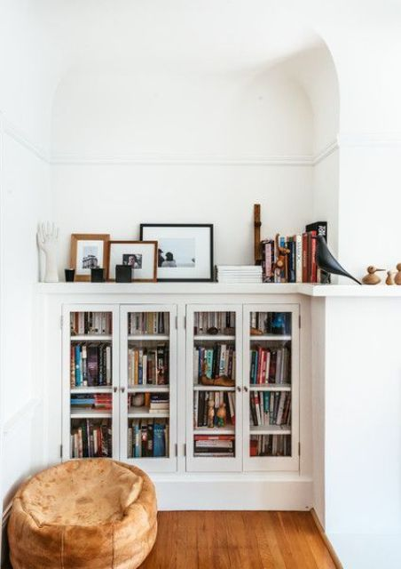 built in bookshelf units with glass doors and a small pouf for a cozy reading nook
