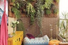 colorful cushions and pillows, a bright chest, a blanket and some greenery in pots on the wall