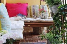 colorful pillows and a boho rug, potted greenery and flowers are bold and cool for a rustic-like balcony