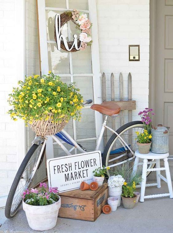 colorful potted and basket blooms, a fake flower wreath and a watering can for a spring porch