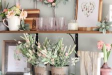 fake pink blooms and greenery, succulents, fresh blooms in pots and pink glasses add a spring touch