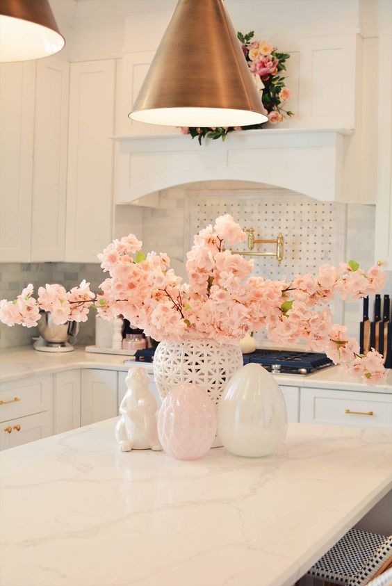 fresh pink blooming branches in a vase and a matching pink wreath make the space look spring-like