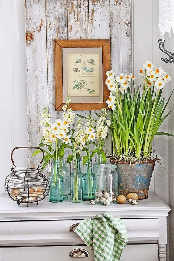 fresh white spring blooms in bottles and jars plus eggs on the table will give an Easter hint to your kitchen decor