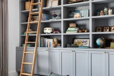 grey built-in bookshelves, blue poufs and a ladder to get all the books comfortably