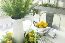 lemons in a bowl, a greenery and lemon wreath, greenery and yellow blooms in a jar make the space look spring-like