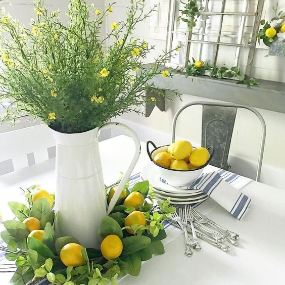 lemons in a bowl, a greenery and lemon wreath, greenery and yellow blooms in a jar make the space look spring like