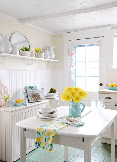 light blue linens, a jug with yellow blooms and some yellow touches make the kitchen spring-like