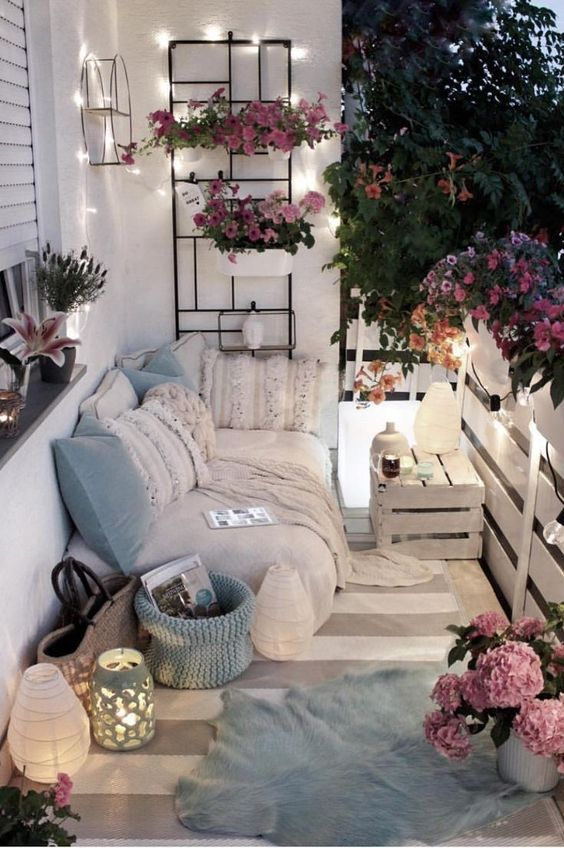 light blue pillows and a basket, potted pink flowers and some lights and lanterns will make your balcony tender and spring-like