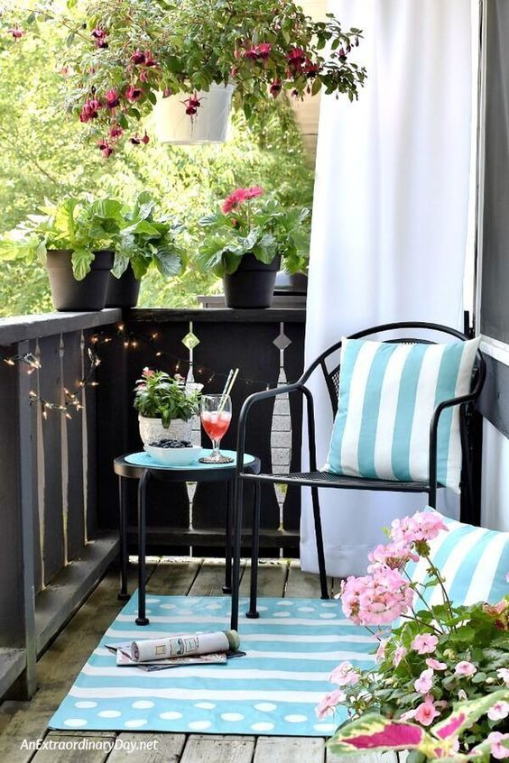 light blue printed pillows and a rug and potted pink flowers turn this balcony in a light inviting space
