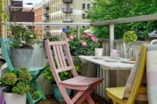 pastel chairs, a colorful rug, potted flowers and greenery for a comfy and chic spring balcony