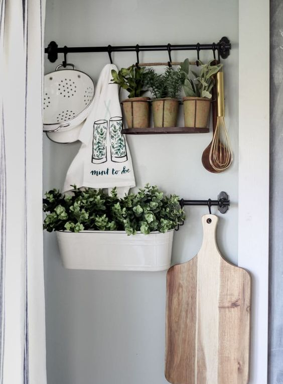 planters and pots with fresh greenery and printed towels make the kitchen fresh and spring-like and do that with style