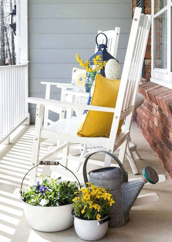 potted blooms, a watering can, bright blooms, colorful pillows for a bright and fun spring porch