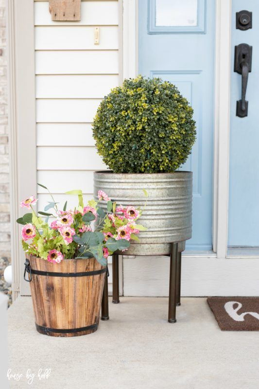 potted fake blooms and greenery and a boxwood topiary will make your porch look fresh and spring