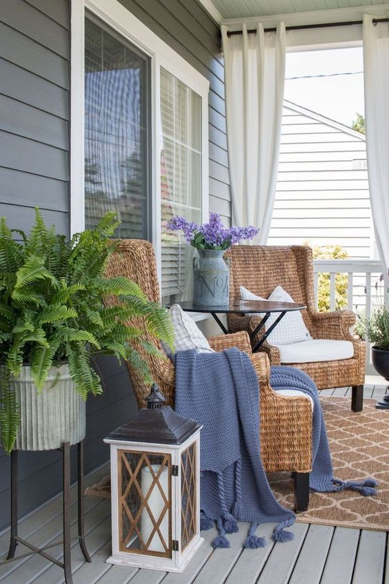 potted ferns, purple blooms in a churn, wicker chairs and candle lanterns for a farmhouse spring porch