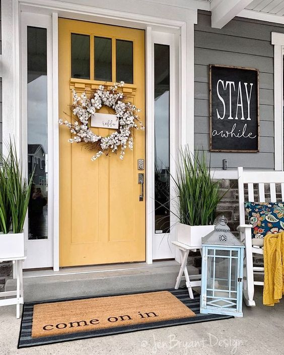 potted grass, a faux bloom wreath and a chalkboard sign for a bright and fun porch
