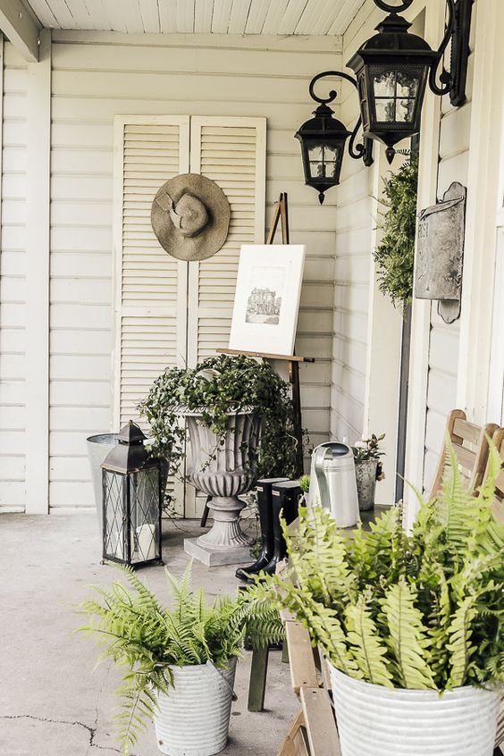 potted greenery and a greenery wreath plus some vintage stuff and lanterns for an elegant spring porch