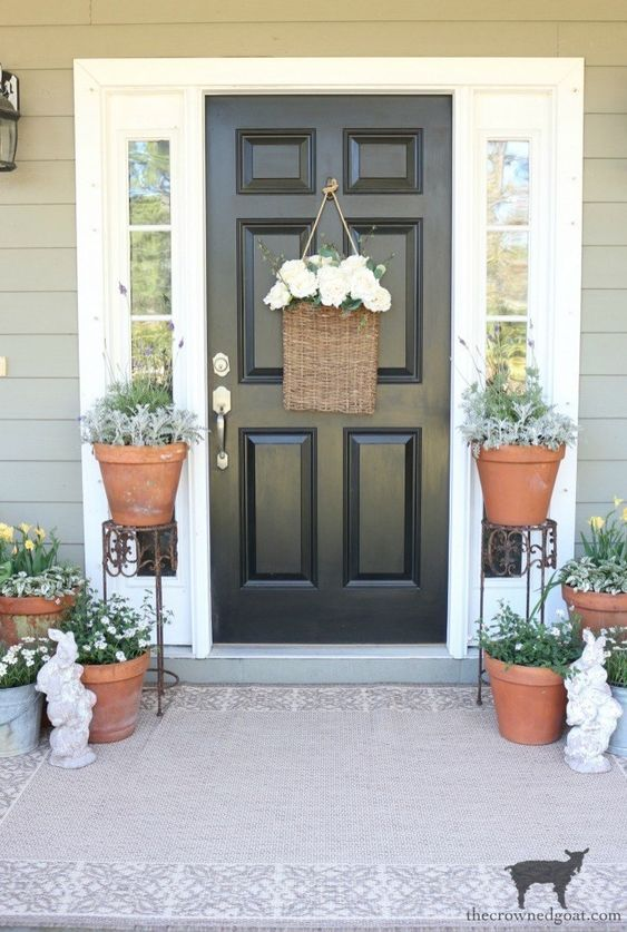 potted greenery and blooms, a basket with white flowers and some bunny statuettes for a farmhouse spring porch