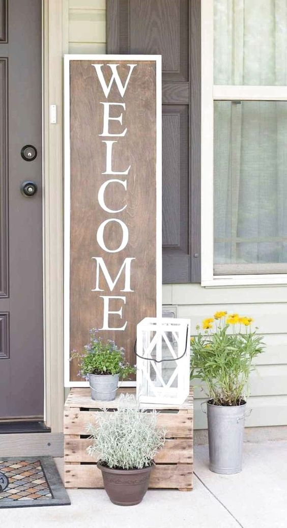 potted greenery and blooms, a candle lantern and a plywood sign for a bright and fun spring porch