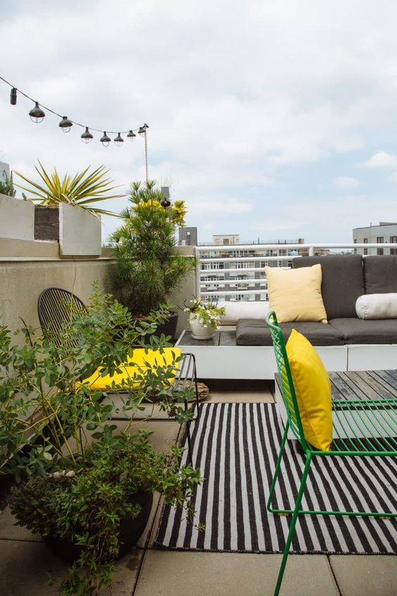 potted greenery and flowers and some sunny yellow touches will enliven even the most laconic balcony