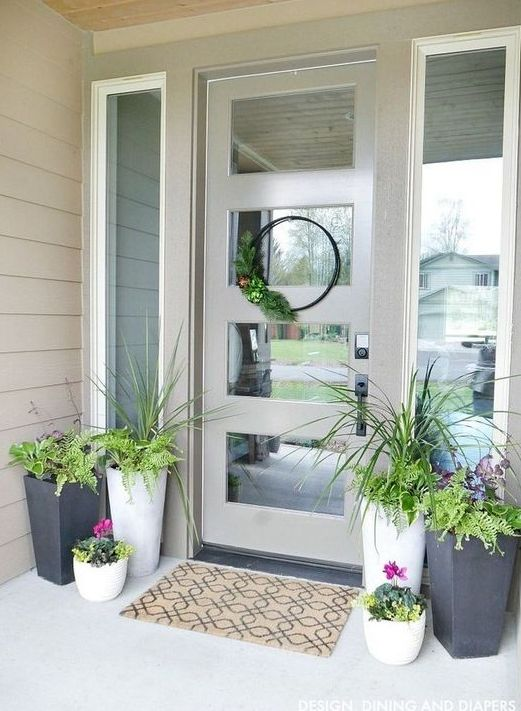 potted greenery, bright blooms and a greenery wreath for a bright spring porch