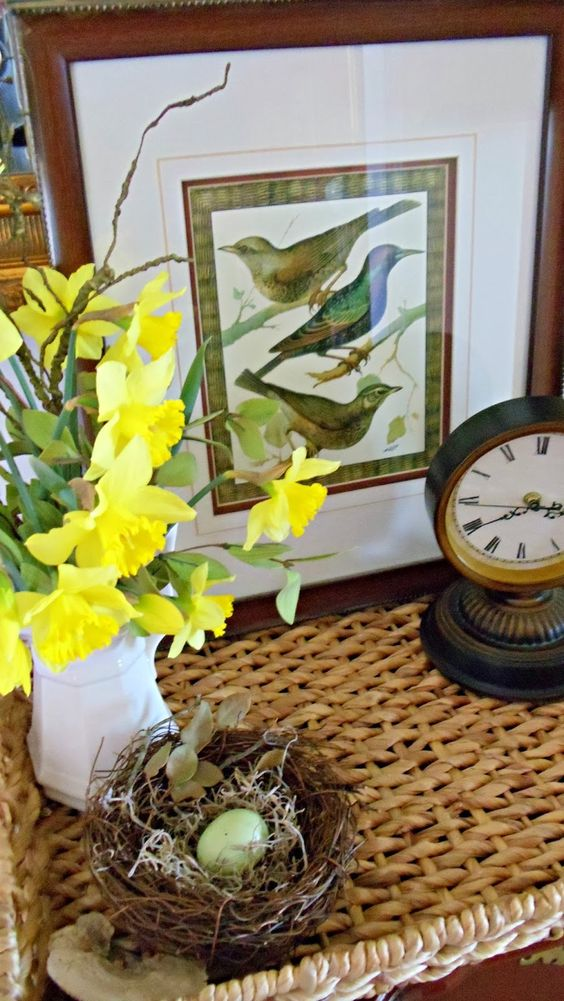 spring home decor with a faux nest and eggs, a white jug with daffodils, a bird print and a clock is refined and chic