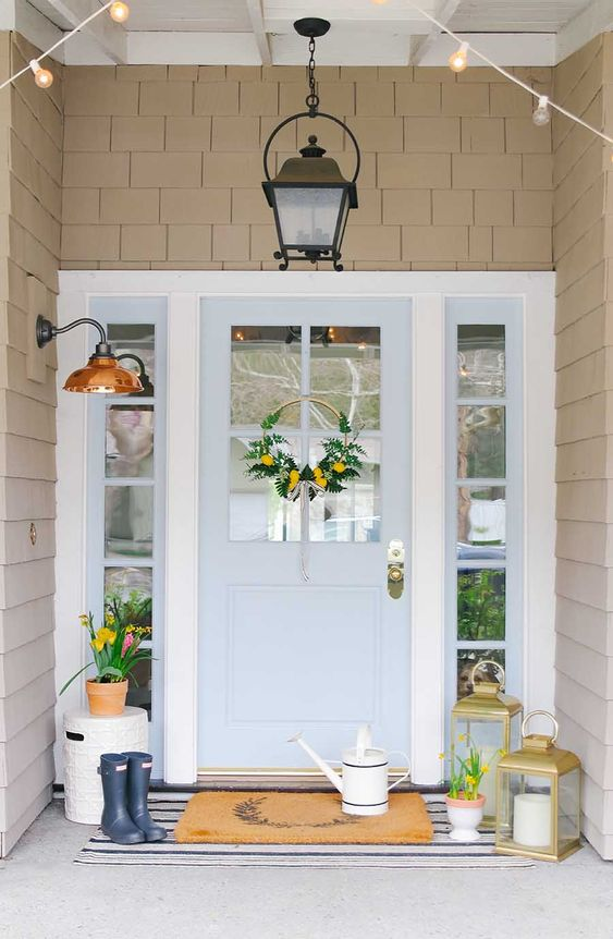stylish spring porch decor with a watering can, candle lanterns, bright blooms in pots and a bright yellow wreath