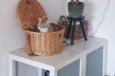 two IKEA Lack tables with paper covers, a cat litter box under them and a basket cat bed on top