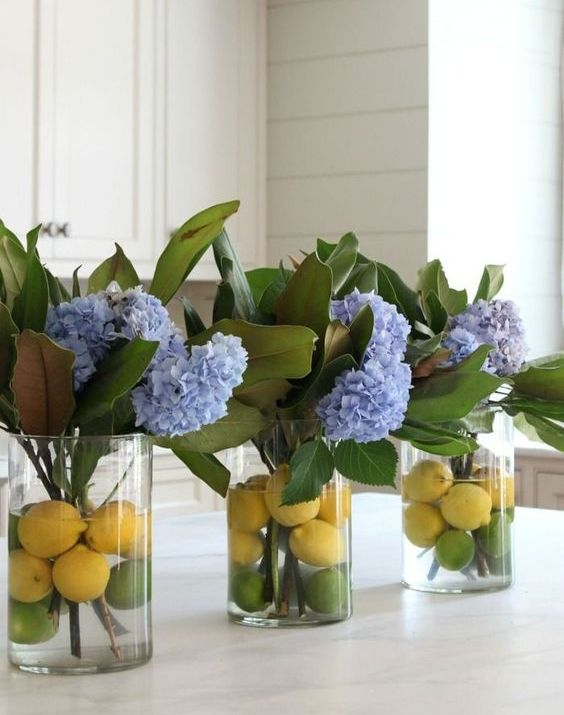 vases with magnolia leaves, blue hydrangeas, lemons and limes add a bright sprign touch to the space