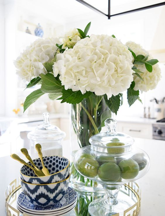 white hydrangeas in a clear vase and limes in a clear jar will make your kitchen feel like spring