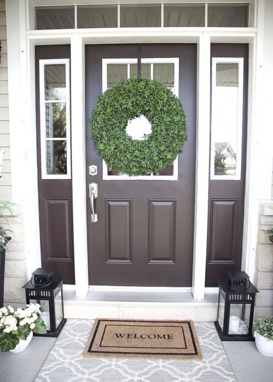 white potted blooms, a boxwood wreath and candle lanterns for a fresh and cool porch