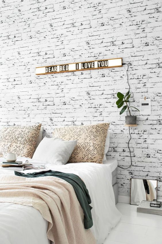 a Nordic bedroom with a whitewashed brick wall, a grey bed, lights and plants is a stylish and welcoming space
