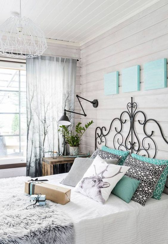 a Nordic bedroom with whitewashed wooden walls, a refined forged bed, wooden nightstands and black wall sconces, a pendant lamp and bright bedding