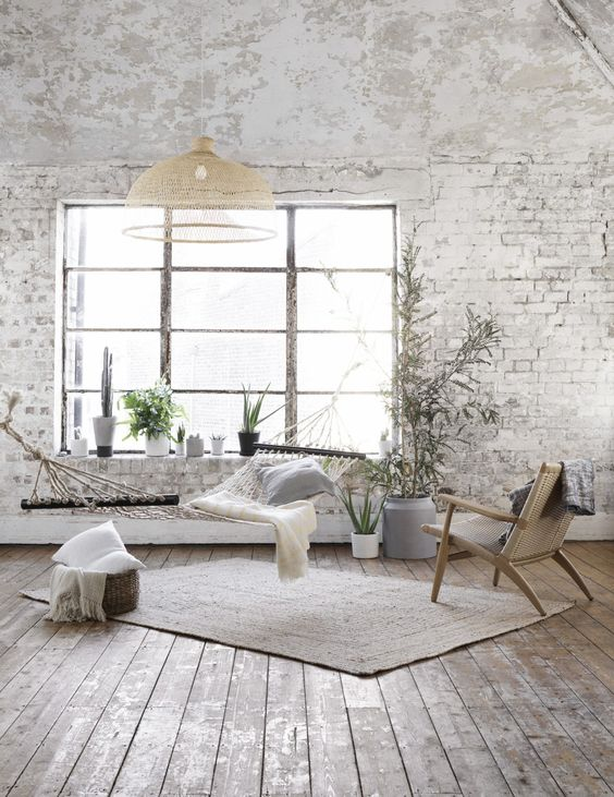 a Nordic living room with whitewashed brick walls, a hammock, a woven chair, a pendant lamp and some pillows