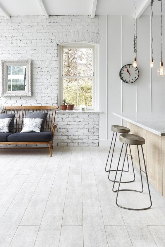 a Nordic space with whitewashed brick walls, a wooden floor, a bar space with stools and a loveseat