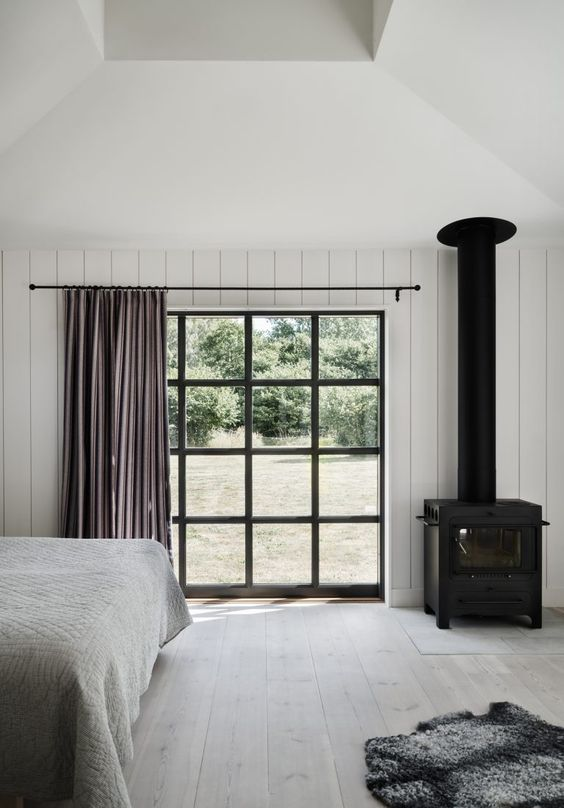a Scandinavian bedroom with white beadboard walls, a whitewashed floor, a framed window and a vintage hearth