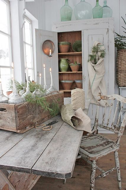 a Scandinavian farmhouse space with a whitewashed storage cupboard, a whitewashed table and a whitewashed and distressed chair