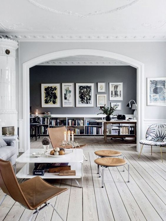 a Scandinavian home with white and black walls, a whitewashed floor and mid-century modern furniture