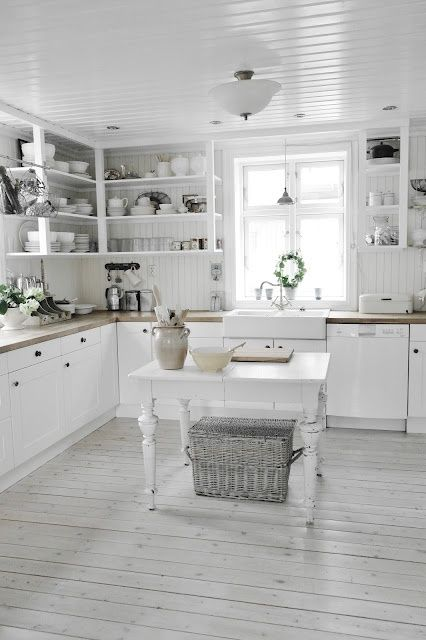 a Scandinavian kitchen with white beadboard walls, whitewashed floors, white cabinets and a vintage table kitchen island