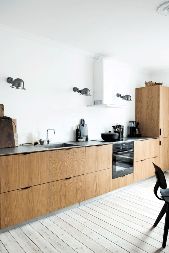 a Scandinavian kitchen with white walls, a whitewashed floor and wooden cabinets plus a concrete countertop