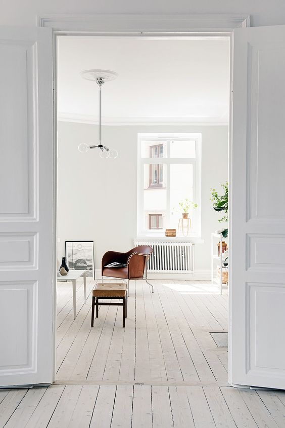 a Scandinavian space with white walls, a whitewashed floor, a white ceiling and leather furniture