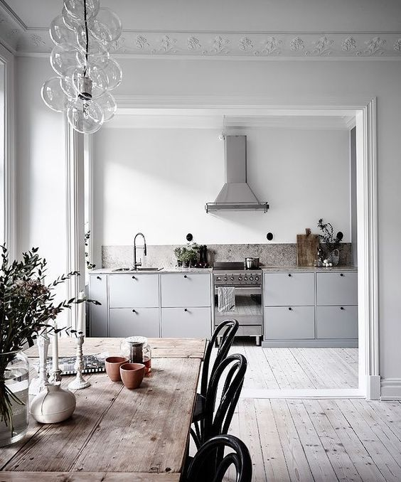 a Scandinavian space with white walls and whitewashed floors, grey cabinets, a wooden table and black chairs