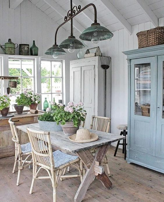 a beautiful Scandinavian veranda with a whitewashed and blue cupboard, with a whitewashed table and rattan chairs, with potted blooms and greenery