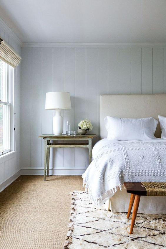 a beautiful coastal bedroom with whitewashed wooden walls, a neutral upholstered bed, vintage benches and tables and neutral bedding