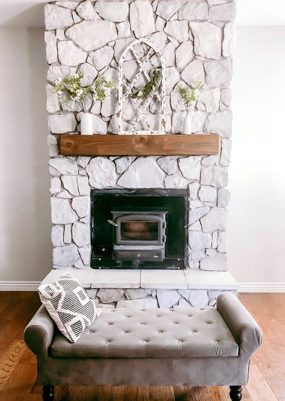 a beautiful whitewashed stone fireplace with a wooden mantel with greenery looks very chic and romantic