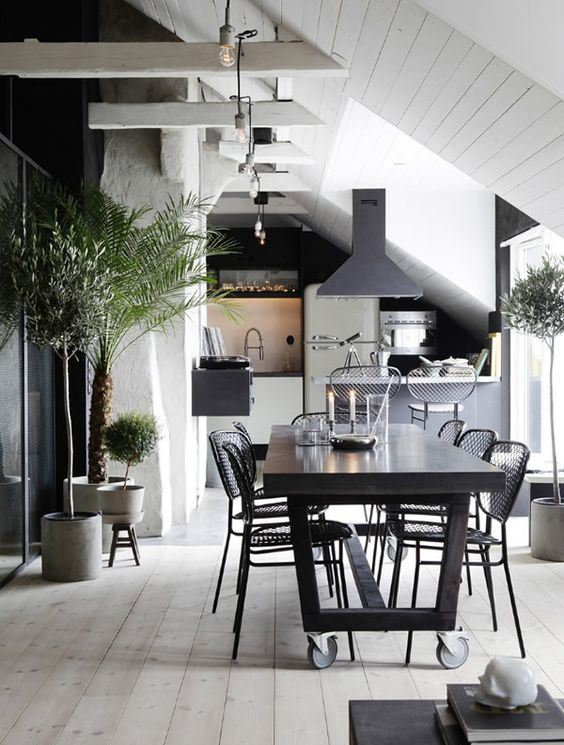 a bold kitchen and dining room, wiht white wood and plaster walls, a whitewashed floor and black furniture and pendant lamps