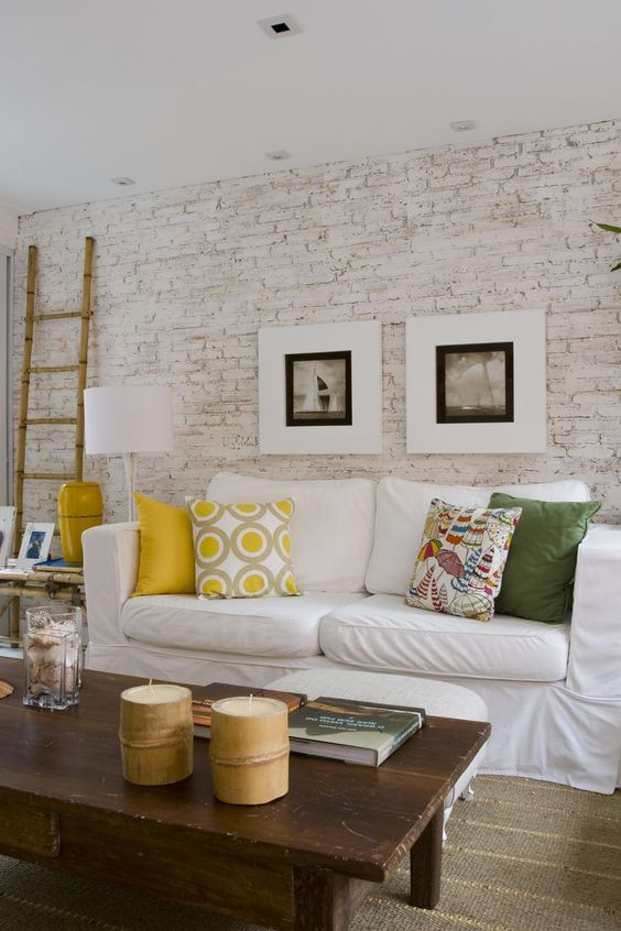 a bright living room with a whitewashed brick walls, a white sofa, colorful pillows, bamboo candles and bright accessories