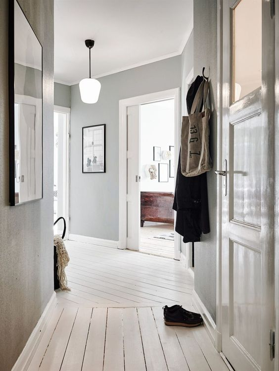 a casual entryway with light grey walls, a whitewashed wooden floor and gorgeous artworks to make the space cooler