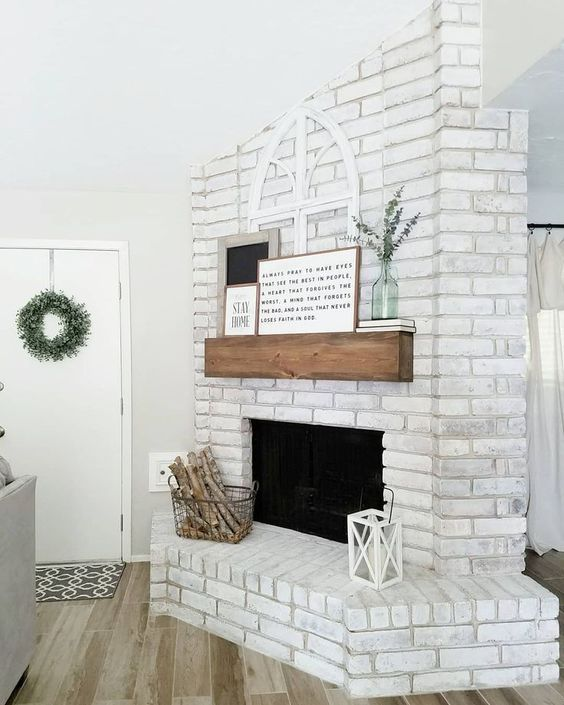 a chic whitewashed brick fireplace with a wooden mantel, artworks and eucalyptus, a wire basket with firewood