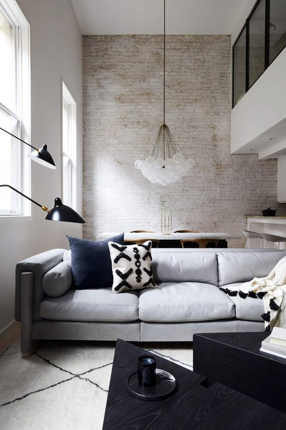 a contemporary living room with a whitewashed wall, chic furniture, a cluster chandelier and black for a touch of drama