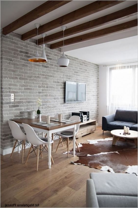 a contemporary space with a living room and a dining zone, a whitewashed brick wall, wooden beams and chic furniture